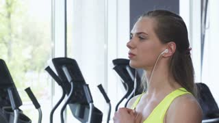 Close up of a gorgeous young sportswoman taking off earphones and wiping her neck with a towel after working out at the gym. Happy healthy fitness woman smiling to the camera.