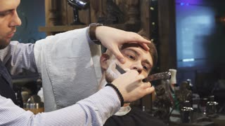 Close up of a handsome young man getting his beard shaved at the barbershop professional barber using a razor shaving his client profession occupation service job barbering styling
