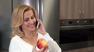 Close up of a mature beautiful happy woman smiling seductively talking on the phone holding an apple housewife healthy eating dieting technology calling mobility carrier concept.