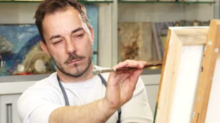 Close up of a professional male artist painting an artwork at his studio examining it carefully. Handsome mature man looking at his painting thoughtfully design creativity equipment experience.