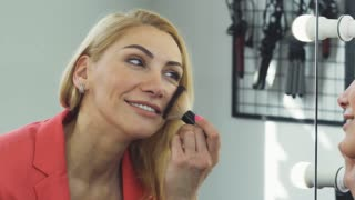 Close up of a stunning beautiful mature woman smiling joyfully applying makeup in front of the mirror beauty cosmetics happiness confidence fashion lifestyle femininity skincare.