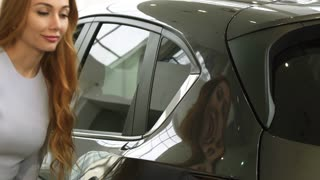 Close up of a stunning beautiful young woman smiling joyfully touching a car while shopping for a new auto at the dealership consumerism retail rental service emotions driving buying