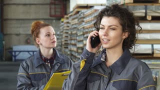Close up of a young attractive female technician smiling joyfully talking on the phone at the distribution warehouse her colleague working on the background. Women, technology.