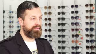 Close up portrait of a happy mature bearded man smiling joyfully putting on glasses showing thumbs up posing at the optometrists store consumerism purchasing buying eyesight.