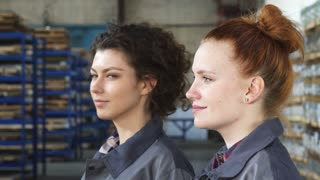 Close up portrait of two beautiful female factory workers or engineers smiling to the camera posing at the production plant. Manufacturing, women, feminism, profession, success.