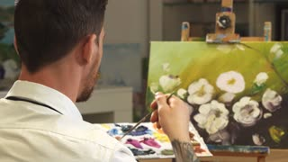 Close up rear view shot of a male professional artist painter painting his artwork at the studio smiling joyfully to the camera over his shoulder occupation creativity design lifestyle hobby concept.