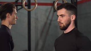 Close up shot of a bearded handsome sportsman concentrating exercising with dumbbells at the gym. Two sportsmen lifting weights training together at crossfit box. Effort, power, masculinity.