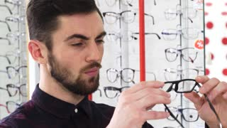 Close up shot of a handsome young bearded male customer examining pair of new glasses while shopping for eyewear at the opticians store eyesight vision eyes fashion consumerism buyer.