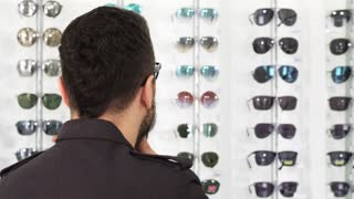 Close up shot of a mature bearded male customer looking to the camera rubbing his beard thoughtfully choosing new sunglasses at the optometrist shop eyewear buying shopping consumer.