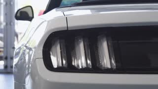 Close up shot of car lights flashing as a male driver getting into the car at the dealership showroom. Mosern cars for sale. Automobile rental service. Technology, automotive industry concept.