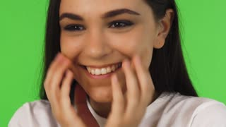 Close up studio portrait of a gorgeous brunette young woman smiling joyfully to the camera. Charming teenage girl cupping her face in her hands. Beauty, youth, positive, wellbeing concept.