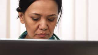 Cropped close up of a beautiful mature Asian female doctor working at her clinic using laptop communication conncetivity technology device health medicine profession scientist