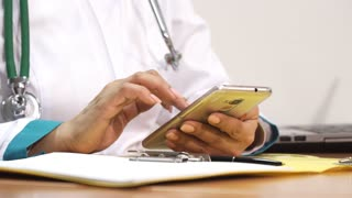 Cropped close up of a female doctor using her smart phone at work making notes filling papers working at the clinic profession occupation medicine mobility gadget carrier healthcare