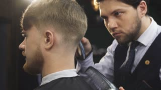 Cropped close up of a handsome professional barber working at his barbership using electrical clipper or trimmer styling hair of his male client service occuaption profession job worker masculine