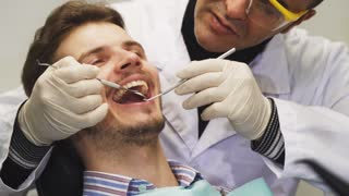 Cropped close up of a handsome young man having his teeth examined by a professional dentist at the clinic medicine health clinical appointment patient dentistry trust occupation service