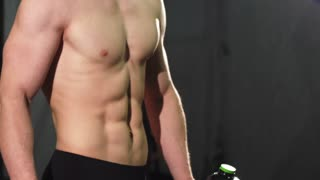 Cropped close up of a shirtless ripped man with sexy muscular body and perfect abs holding water bottle showing thumbs up posing at the gym after powerful workout copy space.