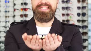 Cropped close up shot of a cheerful bearded man smiling joyfully holding out glasses to the camera eyesight health vision eyewear optometry concept. Consumerism shopping eyewear.
