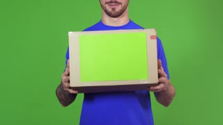 Cropped shot of a bearded smiling professional delivery man posing on green background holding out postal package to the client handing cardboard box to the viewer service concept.