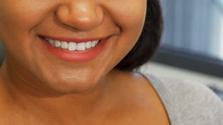 Cropped shot of a cheerful African woman smiling happily with her perfect white teeth, holding a toothbrush near her mouth. Cheerful female with healthy smile. Teeth care, whitening concept.