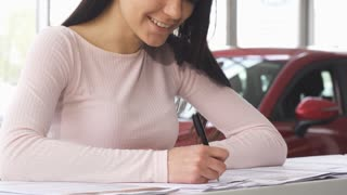 Cropped shot of a cheerful woman smiling while signing papers for her newly bought automobile at the dealership salon. Happy female customer purchasing a new auto. Ownership concept.