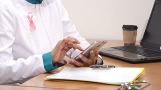 Cropped shot of a female doctor in lab coat with pink ribbon typing messages on her smart phone working at the clinic medicine health awareness prevetion breast cancer mobility connection