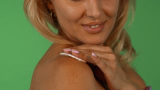 Cropped shot of a gorgeous happy mature woman using cotton pad on her shoulder, moisturizing or cleansing body skin, posing on green chromakey background. Skincare, beauty concept.