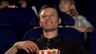 Cropped shot of a handsome young man enjoying movies at the cinema, eating popcorn, smiling to the camera. Attractive cheerful man watching film premiere at the movie theatre.