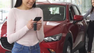 Cropped shot of a happy woman smiling typing messages posing in front of her newly bought car at the dealership salon. Female customer examining automobile on the background.