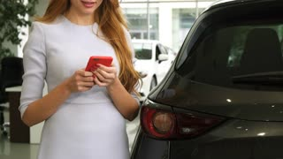 Cropped shot of a happy woman smiling using her smart phone posing near her new automobile at the car dealership consumerism social media sharing online internet driving