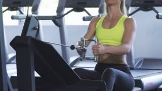 Cropped shot of a sportswoman with sexy fit and toned body workingout on seated cable row machine at the gym studio. Athletic fitness female training her back muscles. Health, body, lifestyle.