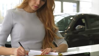 Cropped shot of a woman buying a new car at the dealership salon signing papers client buyer consumerism purchasing agreement signature business retail rental service ownership owner
