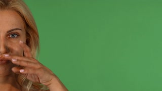 Cropped shot of half of the face of a stunning beautiful mature woman smiling touching her face gently on green chromakey background, copy space on the side. Anti-aging cosmetics concept.
