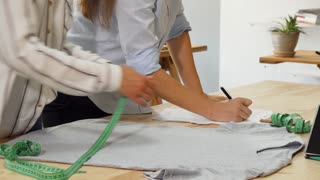 Cropped shot of two female fashion designers working on a clothing piece. Woman designer measuring a t-shirt, while her colleague taking notes. Business, ownership, entrepreneurs concept.