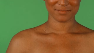 Cropped studio shot of a happy beautiful African woman with perfect smile touching her face sensually. Cheerful mulatto female smiling with her hands to her face.