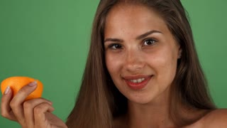 Cropped studio shot of a young beautiful woman with healthy skin, smiling joyfully to the camera, holding an orange, posing on green chromakey. Positivity, lifestyle, health concept.