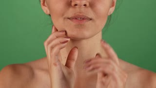 Cropped studio shot of a young woman with soft and smooth silky skin, smiling joyfully, touching her face gently. Attractive happy woman posing on green chromakey background.