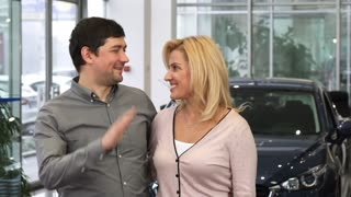 Excited mature couple embracing high fiving laughing joyfully after purchasing a new automobile at the dealership driving travelling family love maturity future travel ownership