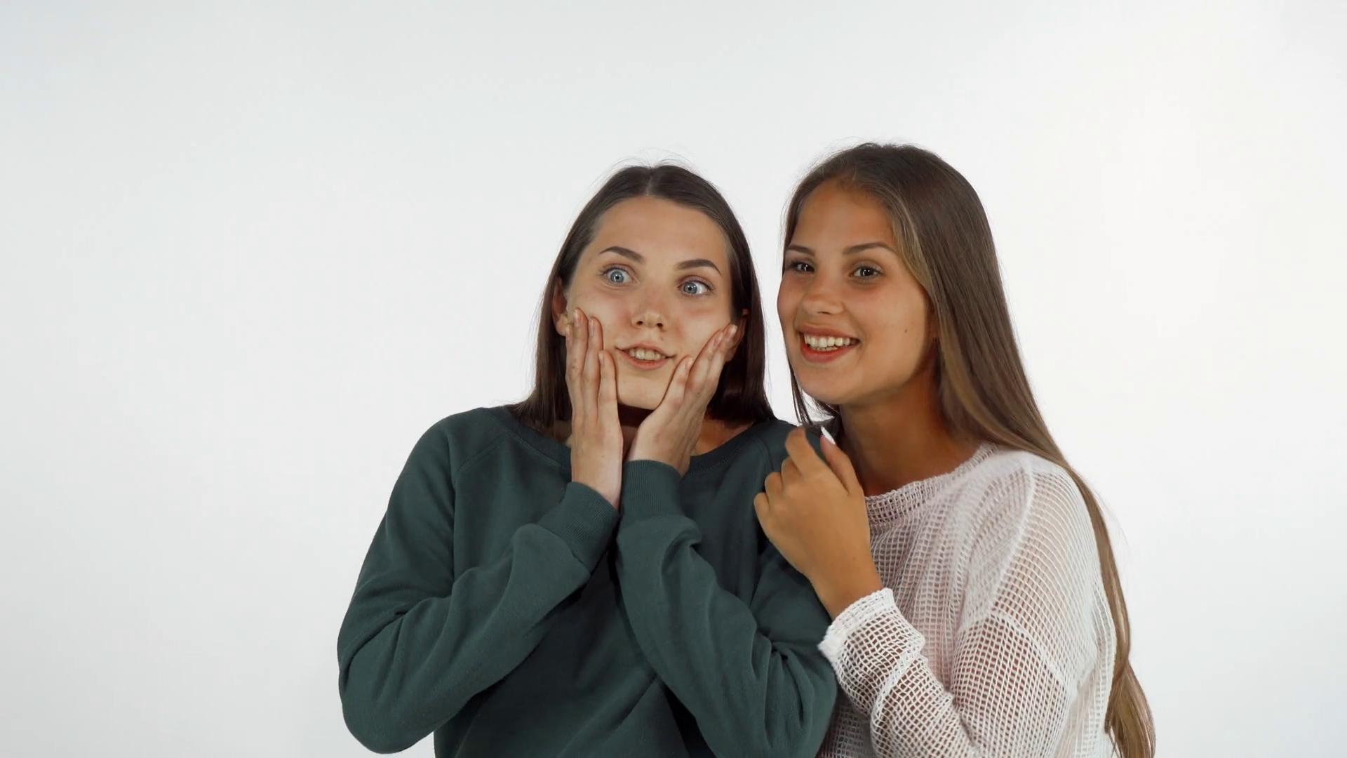 Female friends looking away, laughing looking surprised