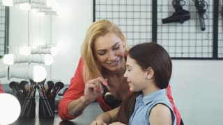 Gorgeous cheerful mature woman playing with her daughter applying make up on her at the beauty salon motherhood parenting family happiness cosmetics emotions kids children togetherness.