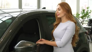 Gorgeous happy young woman smiling showing thumbs up posing near her new automobile at the dealership salon consumerism lifestule luxury buying driver owner positivity