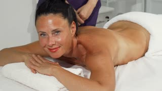 Gorgeous mature woman smiling to the camera, getting relaxing massage at luxurious spa center. Attractive female enjoying soothing massage at the hands of professional masseuse.