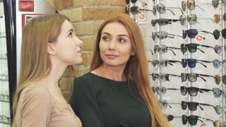 Gorgeous young female friends discussing glasses on display shopping in eyewear store optics optician sight consumerism communication lifestyle retail sale discount offer price leisure