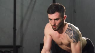 Handsome bearded shirtless muscular man with ripped strong body lifting weights doing back muscles exercise at the gym copy space. Sports, motivation, determination, healthy lifestyle concept.