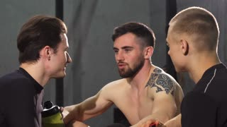 Handsome bearded shirtless sportsman enjoying talking to his friend at the gym after training laughing cheerfully. Group of male friends resting together after working out. Friendship, communication.