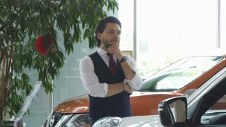 Handsome bearded young man looking thoughtfully at the new car at the dealership salon. Attractive businessman choosing an automobile to buy. Transport, consumerism, rental service.