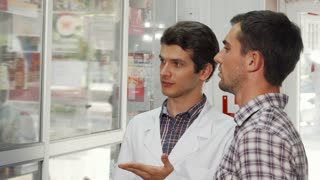 Handsome male professional pharmacist assisting young man at the drugstore. Male clinician and his customer talking at the pharmacy. Consumerism, sales, service concept.
