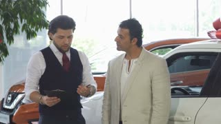 Handsome mature man buying a new automobile at the dealership, signing papers with the salesman. Professional car dealer selling a new automobile to a male customer. Retail, sales.