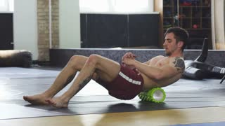 Handsome mma fighter with ripped miscular body resting after powerful training, stretching his back using foam roller. Fitness, sports, active lifestyle. Attractive sportsman relaxing after workout.