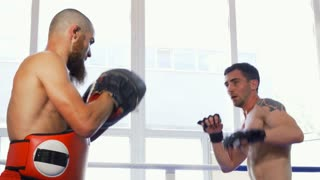 Handsome muscular male mma fighter working out at the fight club. Professional kickboxer sparring with his training partner. Strong male boxer throwing powerful punches.