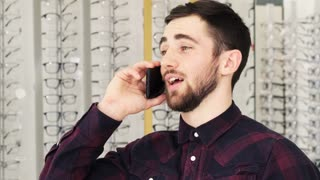 Handsome young bearded man smiling joyfully talking on the phone while shopping at the eyewear store. Happy male customer calling using his mobile communication consumerism.